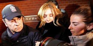 Carlos Ghosn, accompagné de sa femme Carole Ghosn, arrive à son lieu de résidence à Tokyo, le 8 mars 2019.