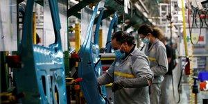 Des ouvriers travaillent sur la ligne d'assemblage de la Renault Zoe dans l'usine de Flins