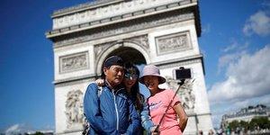 Les touristes s'emparent du point de repère de Paris, l'Arc de Triomphe sur l'avenue des Champs Elysées, en France, le 3 août 2017.