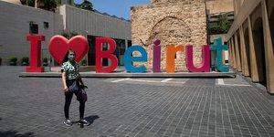 """Liban : une femme portant un masque passe devant un signe """"j'aime Beyrouth"""" alors que les autorités ont imposé un nouveau confinement de deux semaines pour limiter la propagation du coronavirus"""