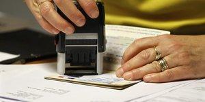 Un employé valide une extension de visa étudiant pour un passeport dans un bureau étranger à Paris. Novembre 2011