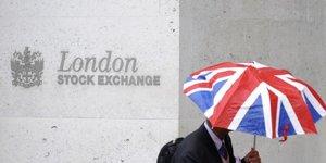 Un travailleur tient en parapluie aux couleurs du Royaume-Uni devant le London Stock Exchange en octobre 2008 Bourse, marchEs financiers